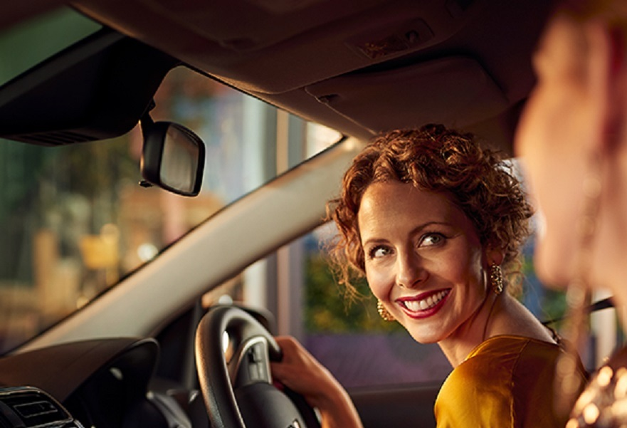 A female driver looking and smiling at female passenger in a Mitsubishi Mirage
