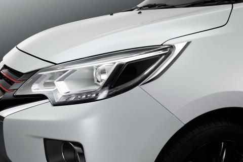 A close up shot of front left headlight of a white Mitsubishi Mirage
