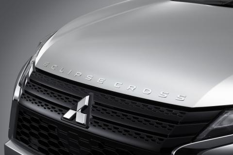 The Mitsubishi Eclipse Cross badge on the front of a vehicle in white