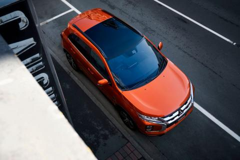 Looking down to an orange Mitsubishi ASX parked on side of the road