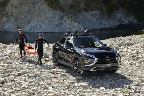 Two people carrying a kayak towards a Mitsubishi Eclipse Cross parked on the river bank