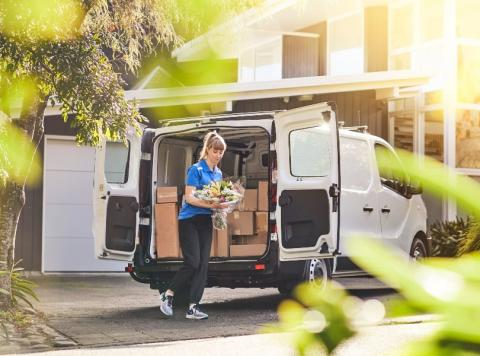 A courier lady delivering a flower bouquet from an Express Van