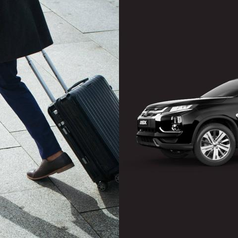 A men dragging a black suitcase and a black Mitsubishi ASX side by side