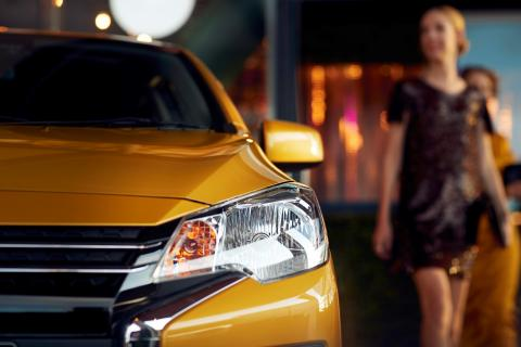 A close up shot of left side headlight of a yellow Mitsubishi Mirage