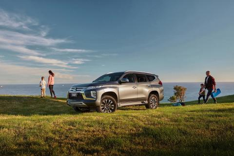 Family about to have picnic and a grey Pajero Sport parked on grass