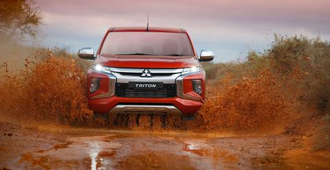 Front view of a red Triton driving through a puddle of mud with mud spraying either side