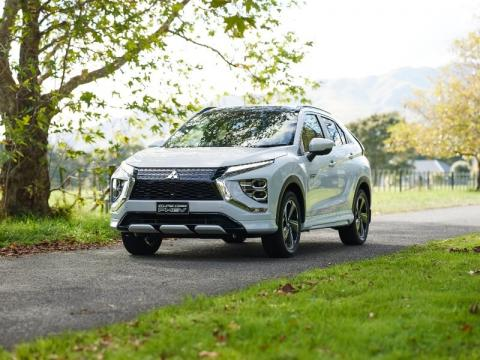 A white Mitsubishi Eclipse Cross PHEV driving down a road in a park